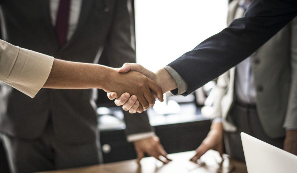 Business professionals shaking hands depicting mediation