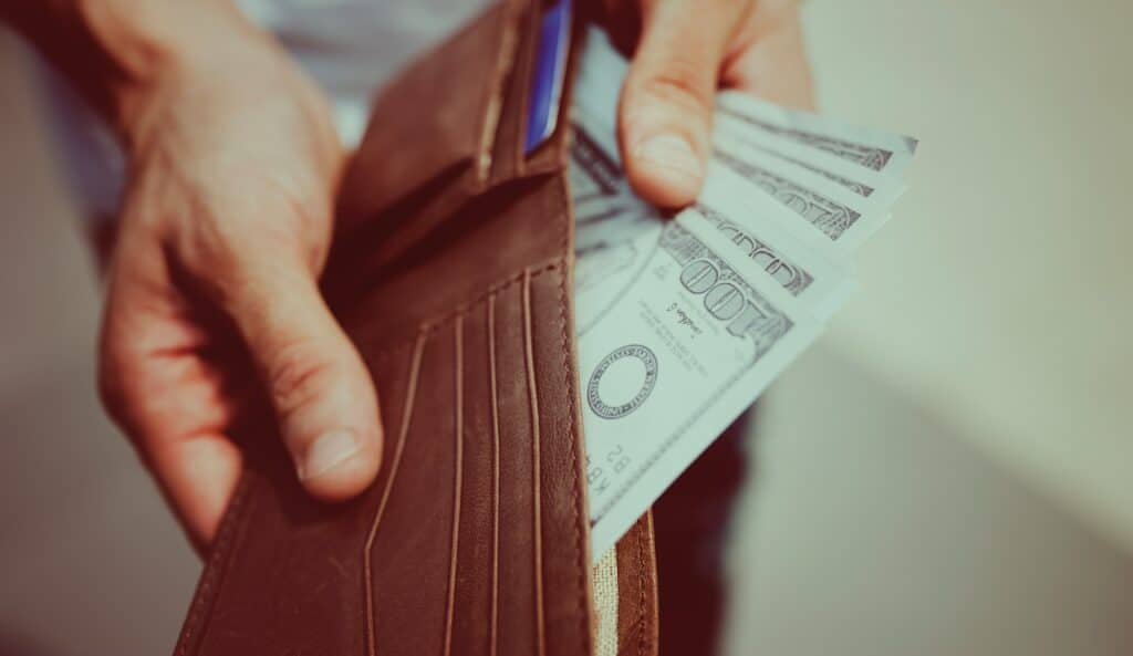 Hundred dollar bills fanned out in wallet