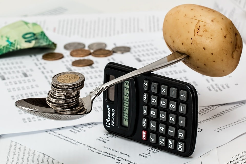 Coins and potato balanced on a spoon and calculator depicting liens