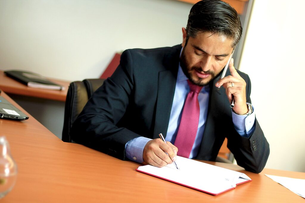 Attorney on cellphone writing notes depicting insurance