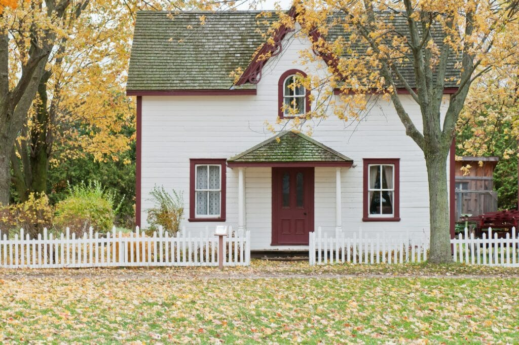 White house with green lawn and fall leaves